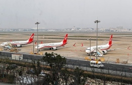 This photo taken on March 11, 2019 shows three Boeing 737 MAX 8 planes from Shanghai Airlines parked at Shanghai Hongqiao International Airport in Shanghai. (Photo by STR / AFP) /