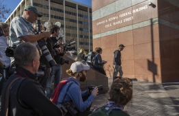 """Members of the press wait outside the Edward R. Roybal Federal Building and US Courthouse where actress Lori Loughlin attended her initial hearing in Los Angeles, California on March 13, 2019. - US actress Lori Loughlin appeared in federal court in downtown Los Angeles on March 13, 2019, in connection with a massive college admissions scam involving other celebrities and top industry CEOs. Bail for the """"Full House"""" star was set at $1 million, the same amount as for her husband, designer Mossimo Giannulli, who has also been charged in the case. The couple were among 50 people indicted on Tuesday in a scam to help children of the American elite gain entry into top US colleges. (Photo by DAVID MCNEW / AFP)"""