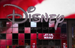 "(FILES) In this file photo taken on December 14, 2017 the Disney logo is displayed outside the Disney Store in Times Square in New York City. - Walt Disney Co. said March 12, 2019 it would close its blockbuster deal for the film and television assets of 21st Century Fox on March 20, a deal likely to reshape the media-entertainment landscape. The $71 billion deal gives Disney the prized 20th Century Fox studios and other media production units.It also vastly reduces the empire of media mogul Rupert Murdoch and his family, who are planning a ""new Fox"" that includes the US broadcast network and the Fox News Channel. (Photo by Drew Angerer / GETTY IMAGES NORTH AMERICA / AFP)"