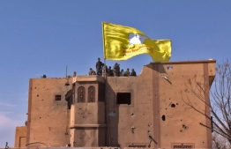 """An image grab released by the Kurdish Ronahi TV on March 23, 2019 shows the US-backed Syrian Democratic Forces (SDF) raising their flag atop a building in the Islamic State group's last bastion in the eastern Syrian village of Baghuz after defeating the jihadist group. - Kurdish-led forces pronounced the death of the Islamic State group's nearly five-year-old """"caliphate"""" on March 23, 2019 after flushing out diehard jihadists from their very last bastion in eastern Syria. (Photo by Handout / RONAHI TV / AFP) / XGTY / == RESTRICTED TO EDITORIAL USE - MANDATORY CREDIT """"AFP PHOTO / HO / RONAHI TV"""" - NO MARKETING NO ADVERTISING CAMPAIGNS - DISTRIBUTED AS A SERVICE TO CLIENTS =="""