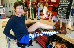 """Evelyne Briand poses with her customized prosthesis at ALGO, a firm specialized in prosthesis in Brest, western France, on March 13, 2019. - """"I did not bear the first prosthesis with foam and a stocking. It was outdated,"""" says Evelyne Briand, showing proudly his left leg decorated with navy blue and white stripes. Now decorated, orthopedic appliances are displayed. (Photo by Fred TANNEAU / AFP)"""