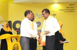 Former President Mohamed Nasheed (L) drapes MDP's 'Agenda 19' sash on Abdul Mughunee, the candidate for the northern constituency of Thinadhoo, Gaafu Dhaalu Atoll. PHOTO: MDP