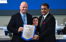 FIFA president Gianni Infantino receives pennant from AFC senior vice president Praful Patel during the Asian Football Confederation (AFC) Congress 2019 in Kuala Lumpur on April 6, 2019. (Photo by SADIQ ASYRAF / AFP)