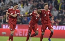 Bayern Munich's Polish forward Robert Lewandowski, Bayern Munich's Austrian defender David Alaba and Bayern Munich's German midfielder Leon Goretzka celebrate after the German first division Bundesliga football match between FC Bayern Munich and BVB Borussia Dortmund in Munich, southern Germany, on April 6, 2019. (Photo by Tobias SCHWARZ / AFP) / RESTRICTIONS: DFL REGULATIONS PROHIBIT ANY USE OF PHOTOGRAPHS AS IMAGE SEQUENCES AND/OR QUASI-VIDEO