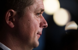 "(FILES) In this file photo taken on September 17, 2018, Andrew Scheer, Conservative Party and Leader of the Official Opposition listens to questions on Parliament Hill in Ottawa, Ontario. - Canada's opposition leader on Sunday, April 7, 2019 revealed Prime Minister Justin Trudeau had threatened him with a defamation case over his comments about a political scandal that has rocked the government months before the country's election. Andrew Scheer, head of the Conservative Party, told a press conference he had received a letter from Trudeau's lawyer accusing him of ""highly defamatory"" comments made in response to a series of documents released by former attorney general Jody Wilson-Raybould at the end of March. (Photo by Lars Hagberg / AFP)"