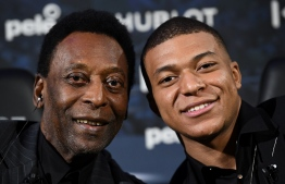 Paris Saint-Germain (PSG) and France national football team forward Kylian Mbappe (R) and Brazilian football legend Pele (L) pose as they take part in a meeting at the Hotel Lutetia in Paris on April 2, 2019. (Photo by FRANCK FIFE / AFP)