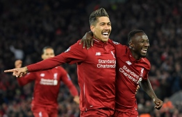 Liverpool's Guinean midfielder Naby Keita (R) celebrates with Liverpool's Brazilian midfielder Roberto Firmino after scoring a goal during the UEFA Champions League quarter-final, first leg football match between Liverpool and FC Porto at Anfield stadium in Liverpool, north-west England on April 9, 2019. (Photo by LLUIS GENE / AFP)