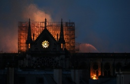 Firefighters douse flames rising from the roof at Notre-Dame Cathedral in Paris on April 15, 2019. - A major fire broke out at the landmark Notre-Dame Cathedral in central Paris sending flames and huge clouds of grey smoke billowing into the sky, the fire service said. The flames and smoke plumed from the spire and roof of the gothic cathedral, visited by millions of people a year, where renovations are currently underway. (Photo by LUDOVIC MARIN / AFP)