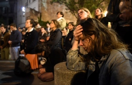 People kneel on the pavement as they pray outside watching flames engulf Notre-Dame Cathedral in Paris on April 15, 2019. - A colossal fire swept through the famed Notre-Dame Cathedral in central Paris on April 15, 2019, causing a spire to collapse and raising fears over the future of the nearly millenium old building and its precious artworks. The fire, which began in the early evening, sent flames and huge clouds of grey smoke billowing into the Paris sky as stunned Parisians and tourists watched on in sheer horror. (Photo by ERIC FEFERBERG / AFP)