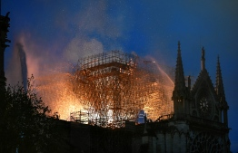 Flames are doused through the scaffolding erected on the roof of the Notre-Dame de Paris Cathedral after a fire broke out on April 15, 2019, in the French capital Paris. - A huge fire swept through the roof of the famed Notre-Dame Cathedral in central Paris on April 15, 2019, sending flames and huge clouds of grey smoke billowing into the sky. The flames and smoke plumed from the spire and roof of the gothic cathedral, visited by millions of people a year. A spokesman for the cathedral told AFP that the wooden structure supporting the roof was being gutted by the blaze. (Photo by STEPHANE DE SAKUTIN / AFP)