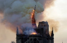 The steeple of the landmark Notre-Dame Cathedral collapses as the cathedral is engulfed in flames in central Paris on April 15, 2019. - A huge fire swept through the roof of the famed Notre-Dame Cathedral in central Paris on April 15, 2019, sending flames and huge clouds of grey smoke billowing into the sky. The flames and smoke plumed from the spire and roof of the gothic cathedral, visited by millions of people a year. A spokesman for the cathedral told AFP that the wooden structure supporting the roof was being gutted by the blaze. (Photo by Geoffroy VAN DER HASSELT / AFP)