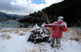This picture taken on March 16, 2019 shows life-size doll depicting a scarecrow pulling a cart in the tiny village of Nagoro in western Japan. - In the tiny village of Nagoro, deep in the mountains of western Japan, the wind howls down a deserted street with not a living soul to be seen. But yet the street appears busy, dotted with life-sized dolls that outnumber humans 10 to one, the product of a one-woman bid to counter the emptiness and loneliness felt in Nagoro, like many Japanese villages decimated by depopulation. PHOTO: KAZUHIRO NOGI / AFP