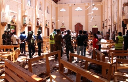 Sri Lankan security personnel walk through debris following an explosion in St Sebastian's Church in Negombo, north of the capital Colombo, on April 21, 2019. - A series of eight devastating bomb blasts ripped through high-end hotels and churches holding Easter services in Sri Lanka on April 21, killing nearly 160 people, including dozens of foreigners. (Photo by STR / AFP)