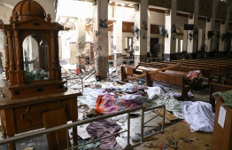 EDITORS NOTE:  / Sri Lankan security personnel walk past dead bodies covered with blankets amid blast debris at St. Anthony's Shrine following an explosion in the church in Kochchikade in Colombo on April 21, 2019. - A string of blasts ripped through high-end hotels and churches holding Easter services in Sri Lanka on April 21, killing at least 156 people, including 35 foreigners. (Photo by ISHARA S. KODIKARA / AFP)