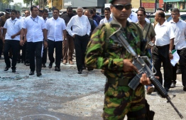 Sri Lankan Prime Minister Ranil Wickremasinghe (C) arrives to visit the site of a bomb attack at St. Anthony's Shrine in Kochchikade in Colombo on April 21, 2019. - A string of blasts ripped through high-end hotels and churches holding Easter services in Sri Lanka on April 21, killing at least 156 people, including 35 foreigners. (Photo by ISHARA S. KODIKARA / AFP)