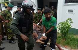 An injured Sri Lankan Special Task Force (STF) member is carried by colleagues after a blast in a house, which was detonated as security forces searched the property, in the Orugodawatta area of the capital Colombo on April 21, 2019. - A string of blasts ripped through high-end hotels and churches holding Easter services in Sri Lanka on April 21, killing at least 156 people, including 35 foreigners. (Photo by ISHARA S.  KODIKARA / AFP)