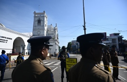 Security personnel stand guard outside St. Anthony's Shrine in Colombo on April 22, 2019, a day after the church was hit in series of bomb blasts targeting churches and luxury hotels in Sri Lanka. (Photo by Jewel SAMAD / AFP)