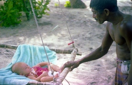 Abdullah, who was a friend of the family, swinging Dhon Kokko on a joali undhoali (traditional swing). PHOTO: FRANK BURNABY