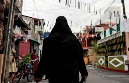 A Muslim woman wearing a hijab walks through a street near St Anthony's Shrine in Kochchikade, Sri Lanka. PHOTO: DANISH SIDDIQUI / REUTERS