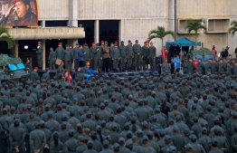 "This handout picture released by Miraflores Palace press office shows Venezuela's President Nicolas Maduro (C) delivering a message to loyal troops at the ""Fuerte Tiuna"" in Caracas, Venezuela on May 2, 2019. - Maduro attends a ""march to reaffirm the absolute loyalty"" of the Venezuelan Army, as opposition leader Juan Guaido continues making calls to oust his government. (Photo by HO / Presidency/JHONN ZERPA / AFP)"