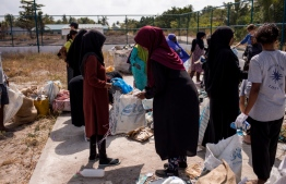 Women collecting and sorting garbage during the clean-up joined held as part of the 'Namoona Baa' initiative. PHOTO: SONEVA FUSHI