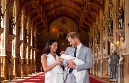 Britain's Prince Harry, Duke of Sussex (R), and his wife Meghan, Duchess of Sussex, pose for a photo with their newborn baby son, Archie Harrison Mountbatten-Windsor, in St George's Hall at Windsor Castle in Windsor, west of London on May 8, 2019. (Photo by Dominic Lipinski / POOL / AFP)