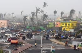 People gather next to storm-damaged buildings and palm trees in Puri in the eastern Indian state of Odisha on May 4, 2019, after Cyclone Fani swept through the area. - Cyclone Fani, one of the biggest to hit India in years, barrelled into Bangladesh on May 4 after leaving a trail of deadly destruction in India. (Photo by Dibyangshu SARKAR / AFP)