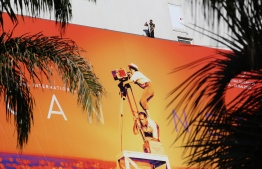 A worker stands above the official poster of the 72nd Cannes Film Festival after it was set up on the facade of the Palais des Festivals in Cannes, southeastern France, on May 12, 2019. - This year's Cannes Film Festival will take place from May 14 until May 25. (Photo by VALERY HACHE / AFP)