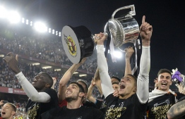 Valencia's Spanish forward Rodrigo Moreno holds the trophy as he celebrates with teammates after their team won the 2019 Spanish Copa del Rey (King's Cup) final football match against Barcelona at the Benito Villamarin stadium in Sevilla on May 25, 2019. (Photo by JOSE JORDAN / AFP)