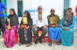 Sobah adorned in medals sitting in between his mother and father holding his trophies. PHOTO: MIHAARU FILES