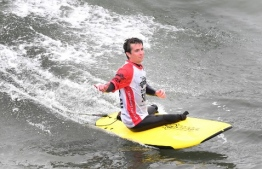 US military veteran Jordan Sisco, injured during his time in Afghanistan, gestures while riding a wave at the Operation Surf event on June 4, 2019 in Huntington Beach, California, hosted by Amazing Surf Adventures in support of wounded active-duty members and veterans from various branches of the US military to help them experience the healing power of the ocean through surfing and camaraderie. (Photo by Frederic J. BROWN / AFP)