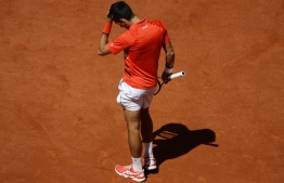 Serbia's Novak Djokovic reacts after losing against Austria's Dominic Thiem at the end of the men's singles semi-final match on day fourteen of The Roland Garros 2019 French Open tennis tournament in Paris on June 8, 2019. (Photo by Thomas SAMSON / AFP)
