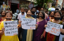Indian supporters of the Bharatiya Janata Party (BJP) hold placards as they observe 'Black day' during a silent protest rally against the recent killings at Sandeshkhali in West Bengal, in Siliguri on June 10, 2019. - Three supporters of India's ruling right-wing party and another from a rival regional party have been killed in a gun battle in West Bengal state, police and a local politician said on June 9. At least 18 others were injured in the clashes that broke out on June 8 in the eastern state that has been on edge since Prime Minister Narendra Modi's Bharatiya Janata Party (BJP) launched an aggressive campaign to win parliamentary seats last year. (Photo by DIPTENDU DUTTA / AFP)