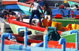 Men fill up diesel containers in a dhoni docked at Male'. PHOTO/UNDP