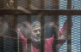 (FILES) In this file photo taken on April 23, 2016 Egypt's ousted Islamist president Mohamed Morsi, wearing a red uniform, gestures from behind the bars during his trial in Cairo at the police academy. - Former Egyptian President Mohamed Morsi died on June 17, 2019 in a Cairo hospital after fainting in a court session, a judicial and security source said. (Photo by KHALED DESOUKI / AFP)