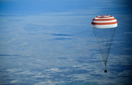 The Soyuz MS-11 capsule carrying the International Space Station (ISS) crew of NASA astronaut Anne McClain, Russian cosmonaut Oleg Kononenko and David Saint-Jacques of the Canadian Space Agency, descends beneath a parachute before landing in a remote area outside the town of Dzhezkazgan (Zhezkazgan), Kazakhstan, on June 25, 2019. (Photo by Alexander NEMENOV / POOL / AFP)