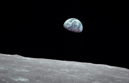 Taken by Apollo 8 crewmember Bill Anders on the morning of December 24, 1968, while in orbit around the Moon, showing the Earth rising for the third time above the lunar horizon.
