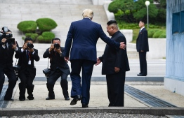 US President Donald Trump steps into the northern side of the Military Demarcation Line that divides North and South Korea, as North Korea's leader Kim Jong Un looks on, in the Joint Security Area (JSA) of Panmunjom in the Demilitarized zone (DMZ) on June 30, 2019. (Photo by Brendan Smialowski / AFP)