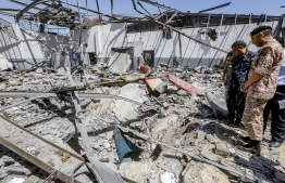 "Military officers of the Libyan Government of National Accord (GNA)inspect damage and debris at a migrant detention centre used by the GNA in the capital Tripoli's suburb of Tajoura on July 3, 2019, following an air strike on a nearby building that left dozens killed the previous night. - Over 40 migrants were killed in an air strike early late on July 2 on their detention centre in a Tripoli suburb blamed on Libyan strongman Khalifa Haftar, who has been trying for three months to seize the capital. The UN said the air strike ""may amount to a war crime"". More than 130 people were also wounded in the in the raid on Tajoura, the statement added. (Photo by Mahmud TURKIA / AFP)"