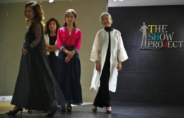 This picture taken on June 11, 2019 shows model Choi Soon-hwa (R) and her colleagues during a modelling class at a model academy in Seoul. - Sleek and straight-backed with elegant grey hair, Choi, 75, is one of a handful of seniors who have become social media and fashion celebrities in a country where intergenerational conflict is mounting as the population ages. (Photo by Jung Yeon-je / AFP) /