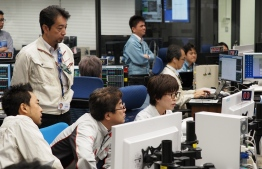 """In this handout photograph taken and released by the Institute of Space and Astronautical Science (ISAS) of Japan Aerospace Exploration Agency (JAXA) on July 10, 2019, shows researchers and employees working at a control room for the Hayabusa2 mission in Sagamihara city, Kanagawa prefecture. - Japan's Hayabusa2 probe began descending on July 10 for its final touchdown on a distant asteroid, hoping to collect samples that could shed light on the evolution of the solar system. (Photo by Yutaka IIJIMA / ISAS-JAXA / AFP) / RESTRICTED TO EDITORIAL USE - MANDATORY CREDIT """"AFP PHOTO / ISAS-JAXA"""" - NO MARKETING NO ADVERTISING CAMPAIGNS - DISTRIBUTED AS A SERVICE TO CLIENTS"""