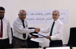 Agreements being exchanged between the company's MD and Housing Ministry's state minister. PHOTO: HOUSING MNISTRY