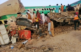 Pakistani rescue personnel and local residents search for victims in a wreck train carriage after two trains collided in Rahim Yar Khan district in Punjab province on July 11, 2019. - At least nine people were killed and more than 60 injured when two trains collided in central Pakistan early July 11, officials said. The incident took place in Rahim yar Khan district in Punjab province when a passenger train coming from the eastern city of Lahore rammed into a goods train that had stopped at a crossing, a senior government official said. (Photo by STR / AFP)