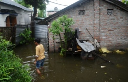 An Indian child wades next to waterlogged houses following monsoon rain in Samarnagar area in Siliguri on July 12, 2019. - Floods from monsoon rains in the north-eastern Indian state of Assam have killed three people and marooned more than 400,000 in 740 villages, officials said on July 11. (Photo by DIPTENDU DUTTA / AFP)