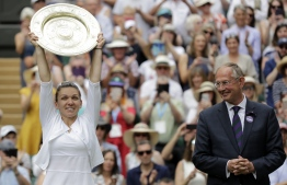 Romania's Simona Halep raises the Venus Rosewater Dish trophy after beating US player Serena Williams during their women's singles final on day twelve of the 2019 Wimbledon Championships at The All England Lawn Tennis Club in Wimbledon, southwest London, on July 13, 2019. (Photo by Ben Curtis / various sources / AFP) /
