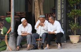 This photo taken on June 4, 2019 shows Uighur men resing in front of a coffee bar in the restored old city area of Kashgar, in China's western Xinjiang region. - In China's Xinjiang, a northwest region tightly controlled by police, authorities have created a parallel universe for tourists and locals -- a place where travellers sightsee just a stone's throw from internment camps. (Photo by GREG BAKER / AFP) /