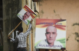 An Indian man holds a placard depicting Kulbhushan Jadhav, an Indian national convicted of spying in Pakistan, in the neighborhood where he grew up, in Mumbai on July 17, 2019. - The International Court of Justice will decide on July 17 on India's bid to remove an alleged spy from death row in Pakistan, in a case that has stoked tensions between the South Asian rivals. (Photo by Indranil MUKHERJEE / AFP)
