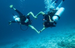 Two divers form a 'heart' during the PADI Women's Dive Day 2019 event held in Maldives. PHOTO/MOODHU GOYYE