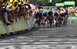 Australia's Caleb Ewan (R) sprints with Slovakia's Peter Sagan (C), wearing the best sprinter's green jersey and other sprinters t o cross first the finish line of the sixteenth stage of the 106th edition of the Tour de France cycling race between Nimes and Nimes, in Nimes, on July 23, 2019. (Photo by JEFF PACHOUD / AFP)
