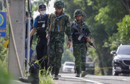 Police investigators and armed soldiers arrive at the site following an attack by militants at a military checkpoint in Pattani on July 24, 2019. - Three government security staff killed along with two villagers in two separated attacks in Thai restive south, army and police said July 24. (Photo by TUWAEDANIYA MERINGING / AFP)